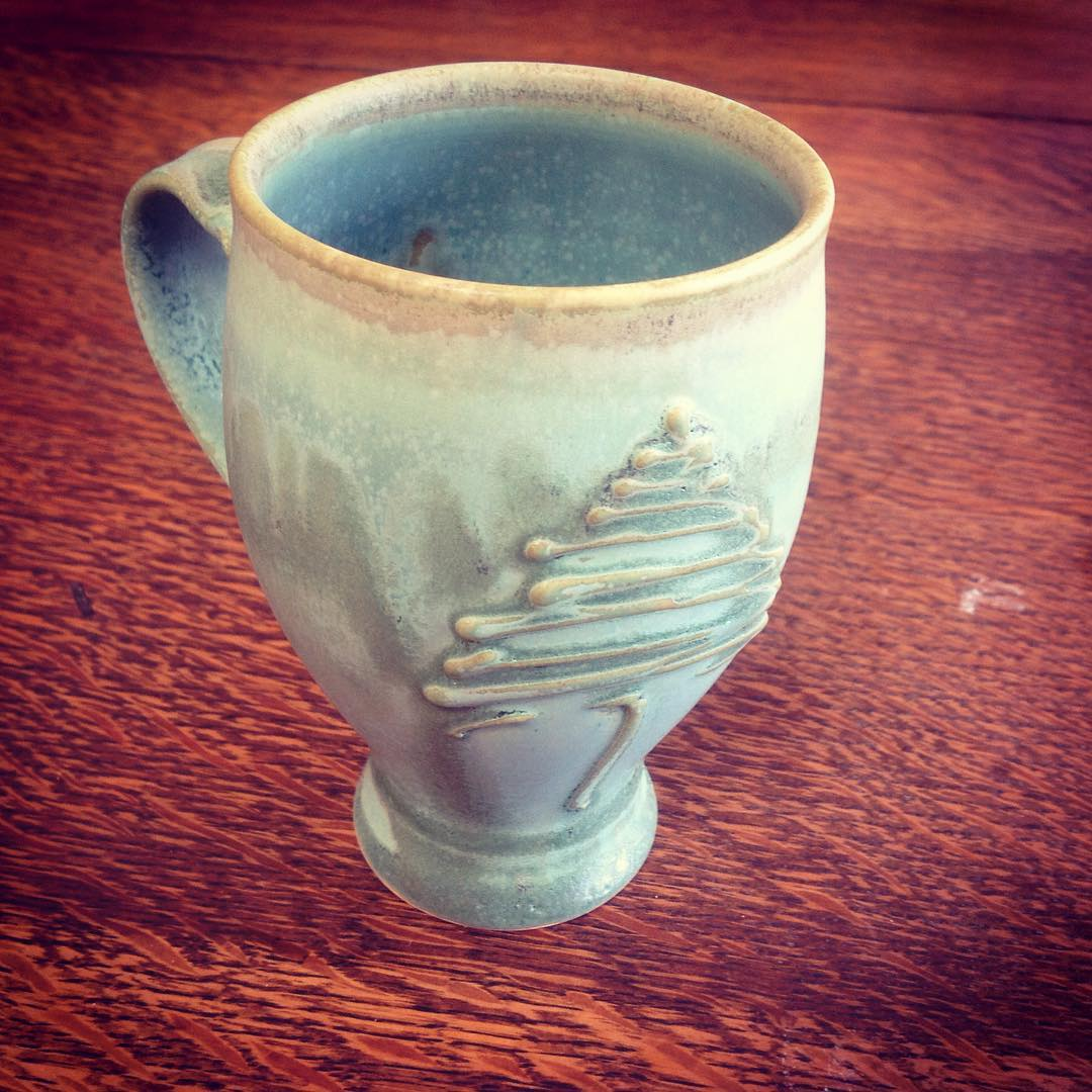 The mug is one of my tulip shaped mugs.  Prongs from the ground and opens like a flower.  I was playing with tree forms of slip trailing a while back and ta daaaa..